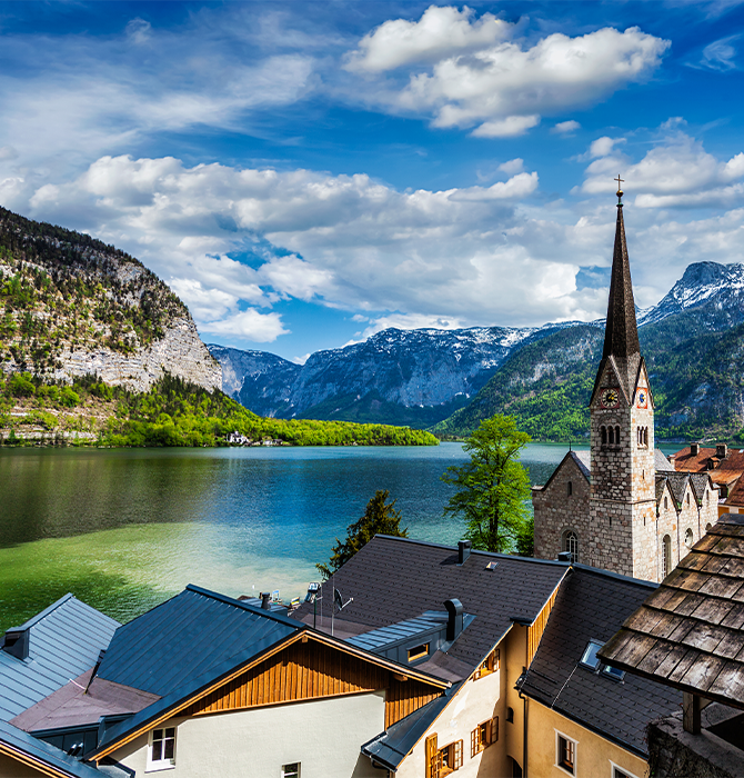 Picturesque View of Town in Austria with Lake and Mountains in the Background - BluJay Customs Management