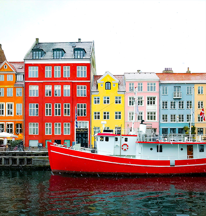Colorful Buildings Grouped Together Along the Water with a Docked Red and White Boat in Denmark