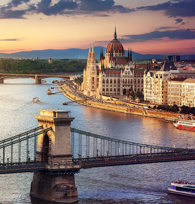 View of City in Hungary with Bridge and Historic Buildings in Background at Sunset