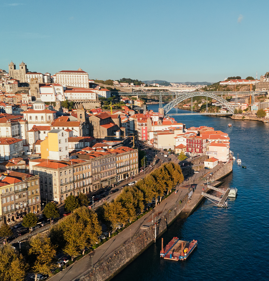 Aerial View of City Along the Shore in Portugal with Bridge in the Background