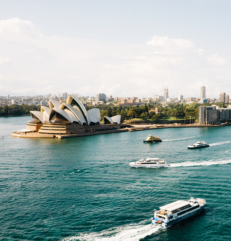 View of Sydney Opera House in Australia with Boats Traveling Around It
